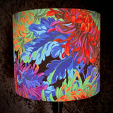Lampshade with rainbow coloured chrysanthemums on a black background