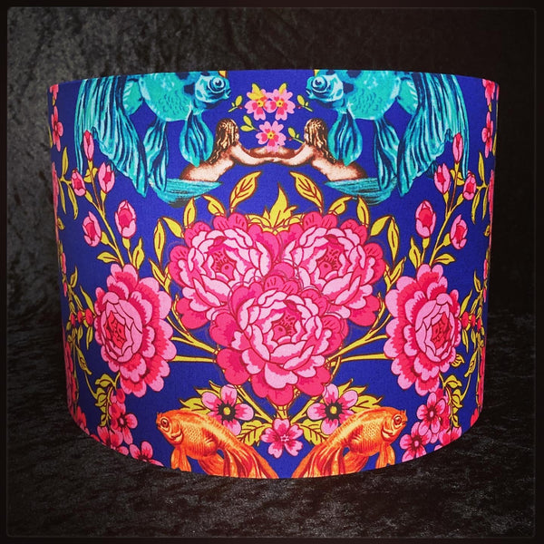 Lampshade featuring brightly coloured mermaids, flowers and fish on a bright blue background