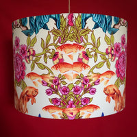 Lampshade featuring brightly coloured mermaids, flowers and fish on a cream background