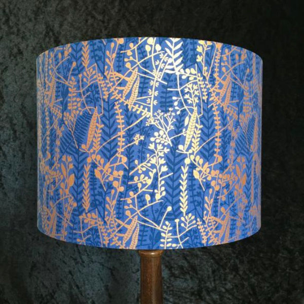 Lampshade featuring dark blue and metallic gold grasses on a blue background