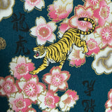 Close up image of a tiger and cherry blossom with gold highlights on a teal background