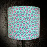 Lampshade with pink and dark teal leopard spots on a light turquoise background