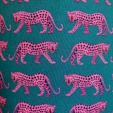 Close up image of lampshade featuring pink leopards on a deep teal background