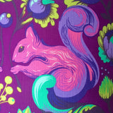 Close up of fabric featuring pink squirrel on a purple background with lime green flourishes