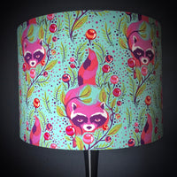 Lampshade featuring pink raccoons on an aqua background