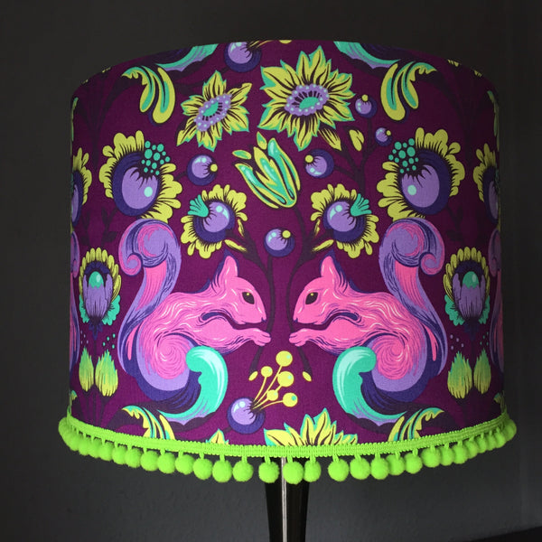 Deep purple lampshade with pink squirrels, yellow and green flowers and lime green pompom trim