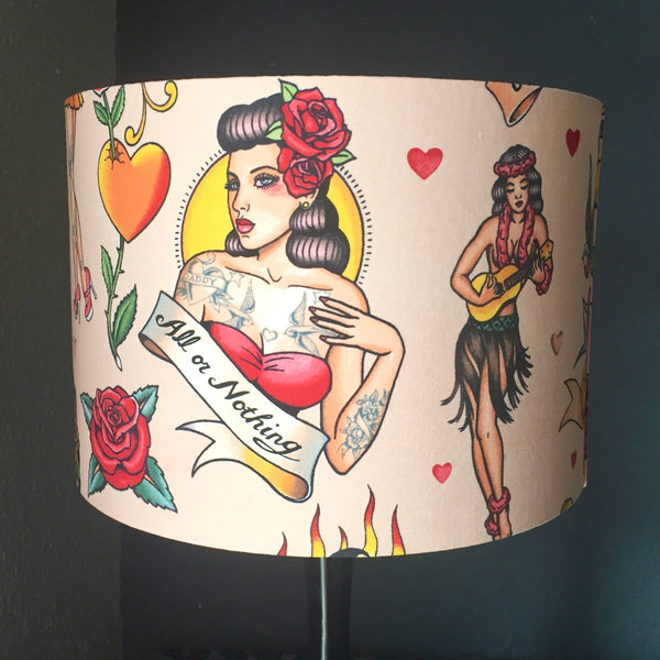 Lampshade featuring vintage tattoo designs of hula girls, hearts, tattoos and swallows on a pink background