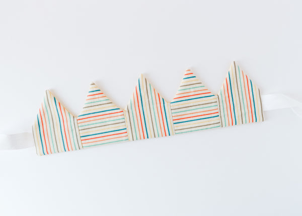 Rainbow stripe fabric crown laying flat on white background