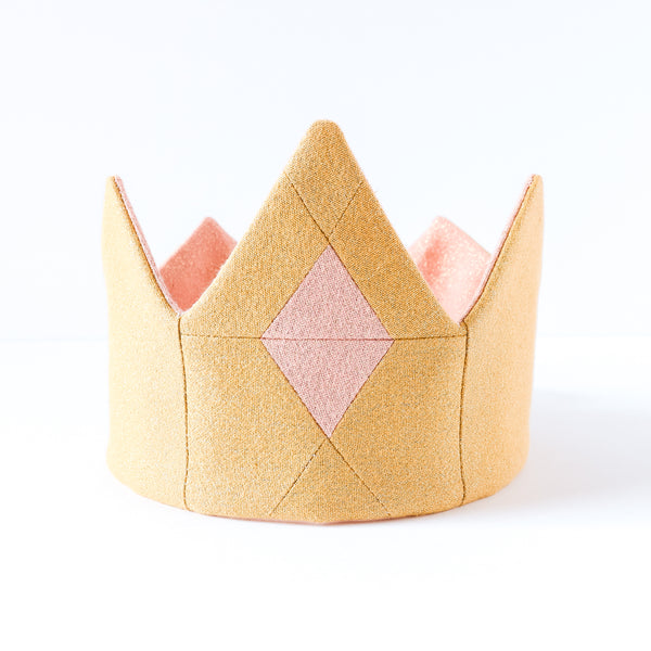 Close up of gold tiara with pink quilted jewel in the center