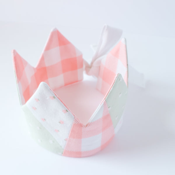 Upper view of pink gingham crown with white and green floral accents