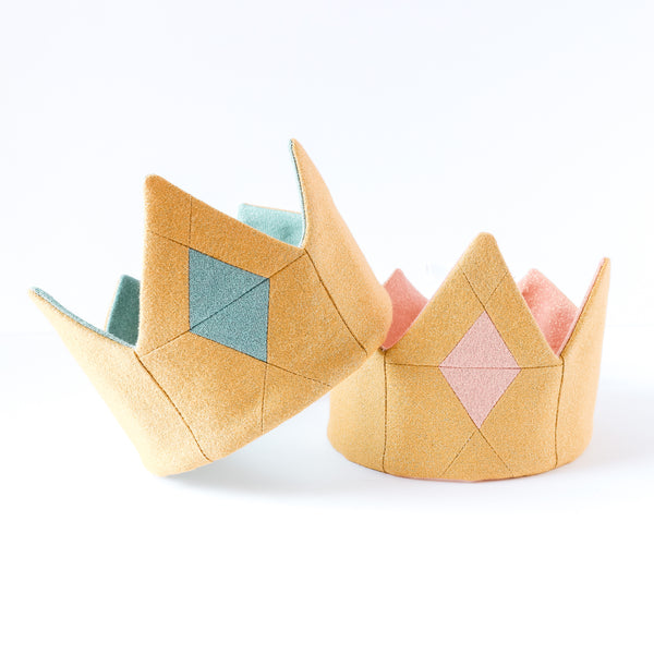 2 gold crowns stacked, 1 with a blue jewel and 1 with a pink jewel