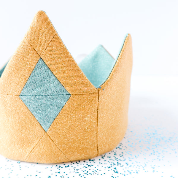 Close up of Gold fabric crown for kids and blue jewel surrounded by blue glitter