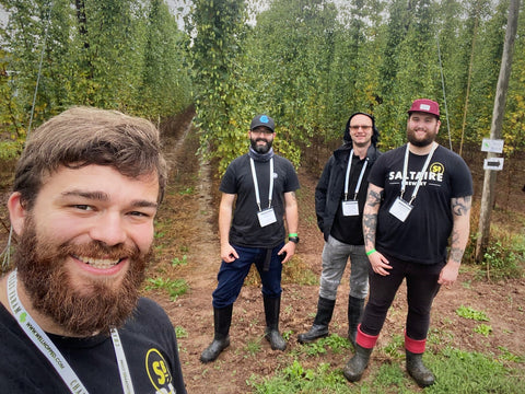 Photo of the brewing team in front of the unpicked rows of hops on the farm