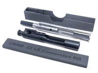 Case for CMMG .22 LR conversion kit bolt open with CMMG and regular AR-15 bolt carrier group next to it