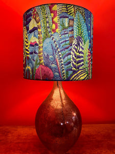 A stunning and unusual lampshade with overlapping feathers in greens, blues and purples for a lamp base or stand.
