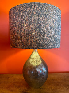 lampshade made using fabric with a thin layer of cork over it. it looks beautiful especially when the light is shining through it