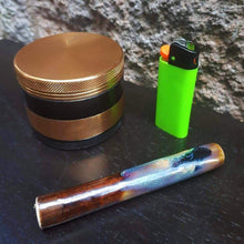 Load image into Gallery viewer, brown/blue chillium pipe with gold grinder and green lighter on black table/brick wall