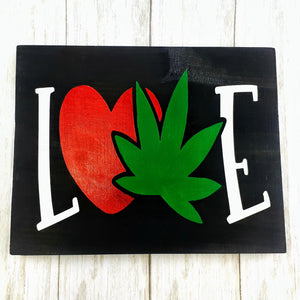 """LOVE"" Cannabis Leaf Wood Sign with White letters L & E, green leaf and red heart on black background"