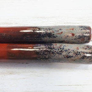 Close up of 2 Grey and red mottled chillium pipe on light wood background
