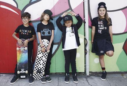 4 Kids stand with their backs against a painted mural wearing StereoType Kids clothing in San Francisco