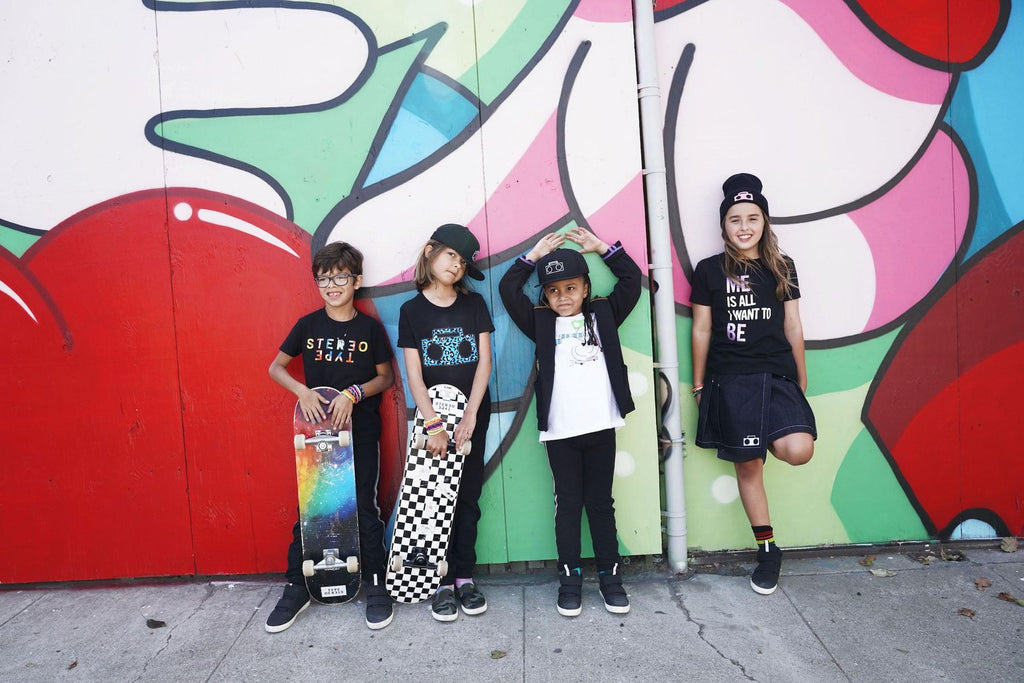 5 kids in Stereotype Kids clothing lean against a muraled wall in the dogpatch in SF