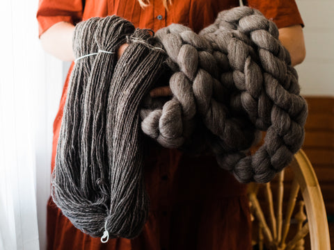 arms holding skeins of handspun yarn and unspun charcoal coloured combed top
