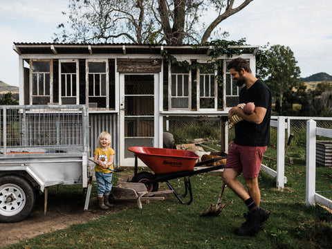 father and daughter shovelling dirt this darling home