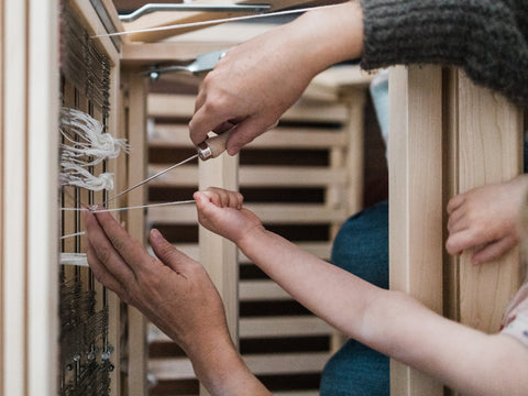 mother and daughter hands threading baby wolf loom aerial view - this darling home