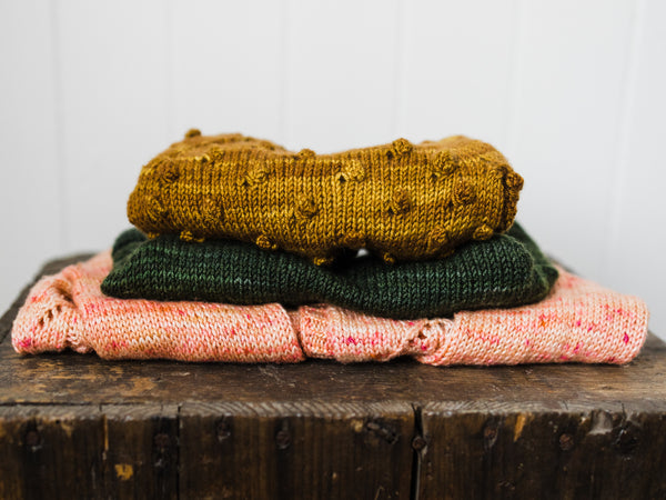 pile of hand knit children's sweaters by Samantha Gehrmann of This Darling Home