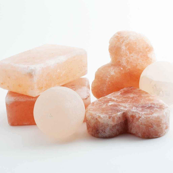 Picture of approximately 6 different bars of Himalayan Salt Soap. These are a combination of Pink Himalayan Salt soap and a lighter white looking salt soap. In a variety of shapes and sizes, 2 rectangular bars of Pink Himalayan Salt Soap, 2 Heart Shaped Pink Himalayan Salt Soaps ad 2 pale balls of himalayan salt soap