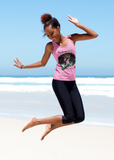 Black young adult on a beach jumping up in the air in joy, wearing a cotton pink tank top with a large picture of a black woman with a beautiful afro, wearing a crown. Slogan at the top says Melanin Queen, at the bottom says Diva, living my Blessed Life, with the RoyalDrip Periodt. Logo. Model is wearing black leggings