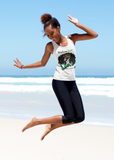 Black young adult on a beach jumping up in the air in joy, wearing a white tank top with a large picture of a black woman with a beautiful afro, wearing a crown. Slogan at the top says Melanin Queen, at the bottom says Diva, living my Blessed Life, with the RoyalDrip Periodt. Logo. Model is wearing black leggings
