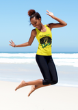 Black young adult on a beach jumping up in the air in joy, wearing a yellow tank top with a large picture of a black woman with a beautiful afro, wearing a crown. Slogan at the top says Melanin Queen, at the bottom says Diva, living my Blessed Life, with the RoyalDrip Periodt. Logo. Model is wearing black leggings