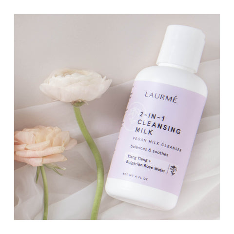 2-in-1 cleansing milk laying next to roses
