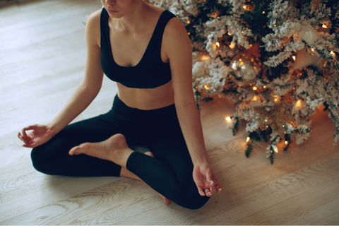 Woman practicing yoga indoors in front of a Christmas Tree | TRIBE Yoga