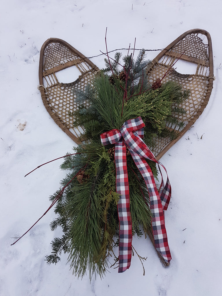 Vintage snowshoes with evergreens