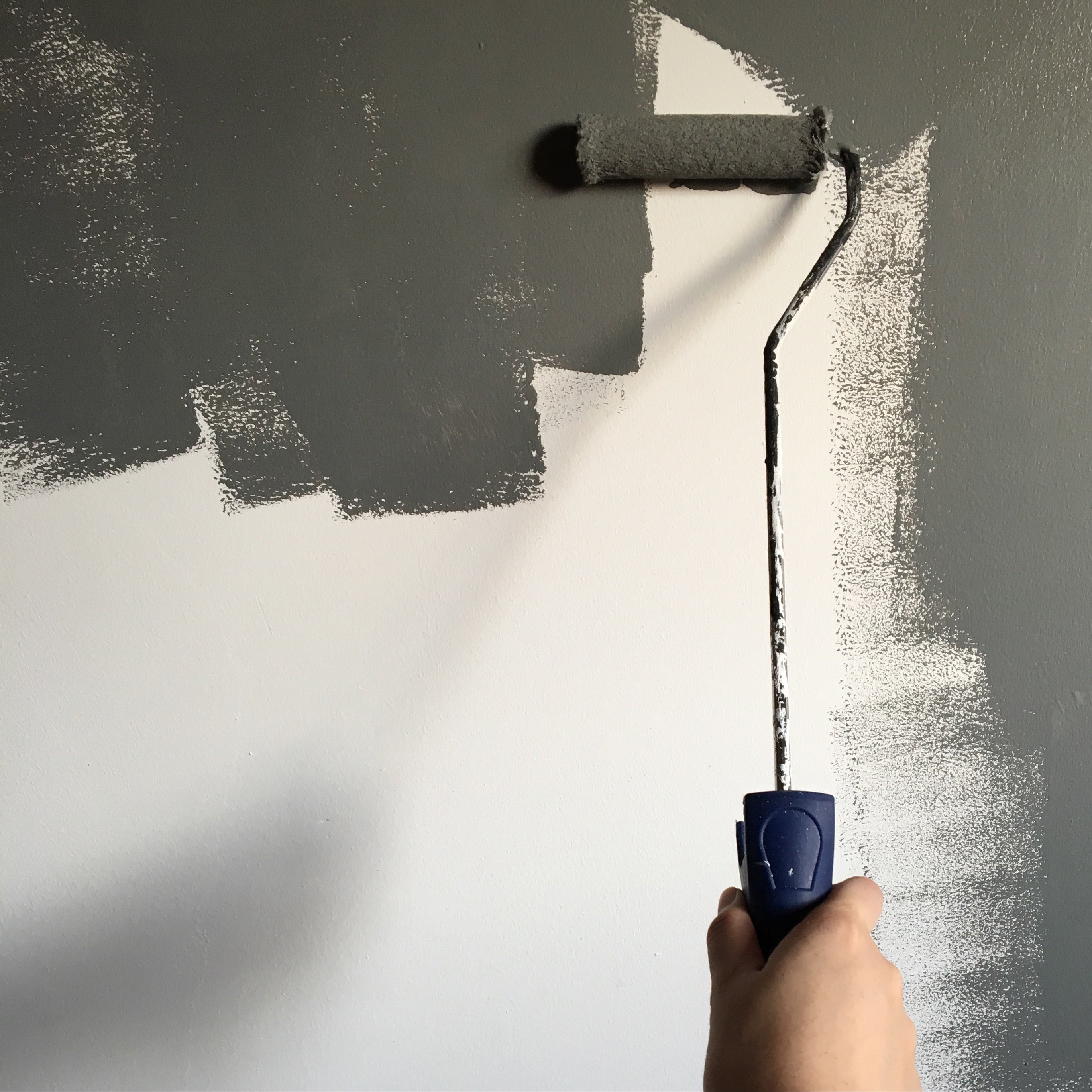 person-holding-paint-roller-while-painting-the-wall