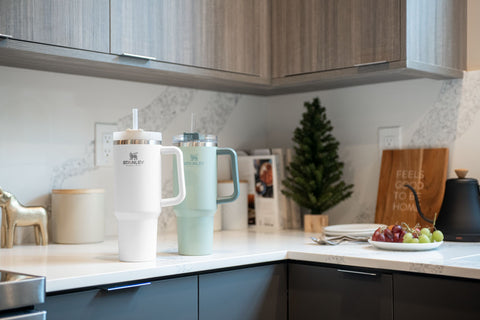 Stanley Adventure Quencher Travel Tumblers in Cream and Desert Sage on a kitchen counter