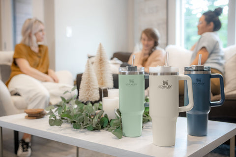 3 Stanley Adventure Quencher Travel Tumblers in Desert Sage, Cream and Abyss on a coffee table