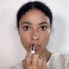 Applying the Glossier Generation G Sheer Matte Lipstick in Cake on medium dark skin