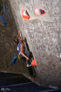Canadian competitive National Team climber Guy McNamee on red holds during a bouldering competition.