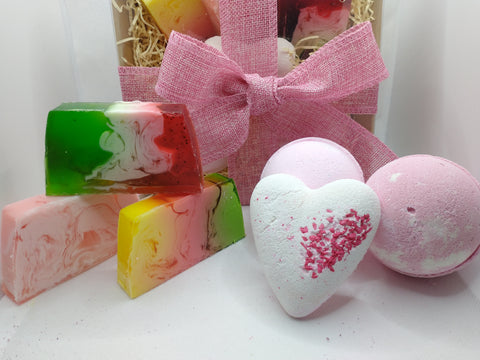 the gift set is shown here with products stacked in front there are 3 beautiful hand made soaps in pink green red and white and yellow pink and green 2 large pink bath bombs and a pretty white bath fizzer in a heart shape with pink flecks
