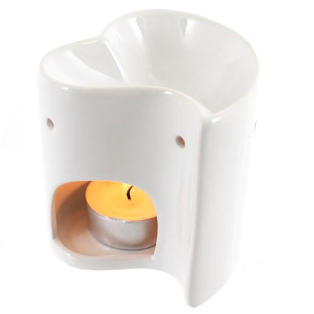White Heart shaped oil and wax melt burner shown with tealight candle alight inside and glowing