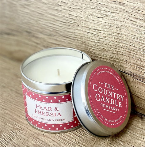 silver round tin with pink and white polka dot band labelled Pear & Freesia with pink sticker on lid with writing The Country Candle Candle Company