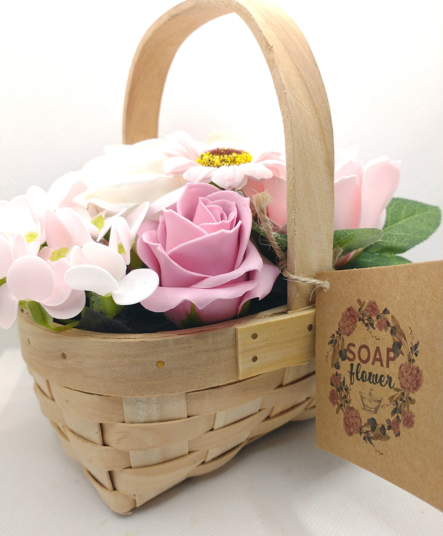 soap flowers shown in wicker basket with kraft tag showing wording Soap Flowers and contents including pink roses white roses and pink sunflowers with green foliage