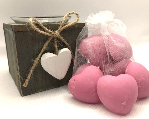 Cute pink heart shaped soy wax melts shown sat against a white clear organza bag containing pink heart shaped soy wax melts