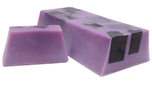 A Violet soap slice with black soap squares shown in the upper half of the bar photographed nect to the full soap loaf which is a deep violet in colour with black soap squares shown throughout the loaf