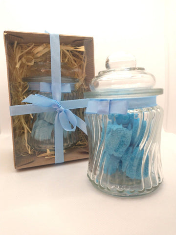 Gift Set with ribbon showing contents in front of a glass jar containing blue bath bombs