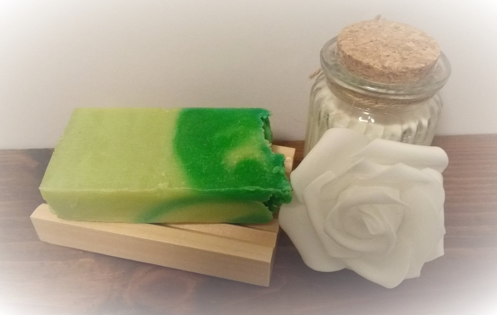 Green Soap slice on soap dish displayed next to rose and candle
