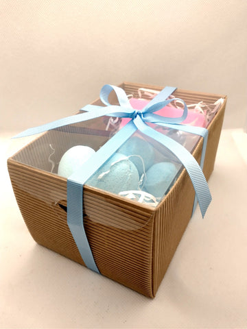 A beautifully handtied light blue ribbon tied off in a bow around a brown corrugated kraft gift box with a clear lid showing contents inside of a light blue heart shaped bath bomb a white organza bag containing light blue mini bath bombs and a white pink and blue striped handmade soap slice